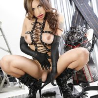 Solo shemale Angeles Cid jerks her hard cock wearing black velvet gloves and boots