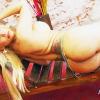 Tattooed blonde tranny Angeles Cid lays totally naked on the frame of a lounge chair
