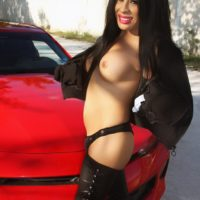 Dark haired Latina tranny Tania Quintilla touts her big tits in thigh high leather boots