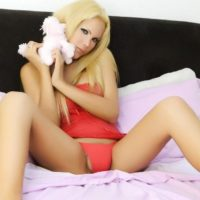 Gorgeous blonde shemale Mlla Viasotti shows her bare legs in a short red dress