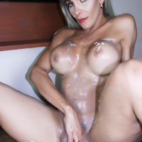 Long legged and busty tranny Nelly Ochoa covers her naked body in body lotion