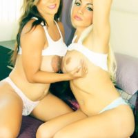Busty blonde shemale Angeles Cid and TS Naomi Chi fondle each other on a bed