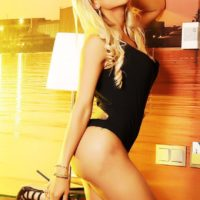 hot blonde tranny Angeles Cid flaunts her booty in a black swimsuit and boots