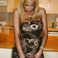 Sexy blonde T-girl Milla Viasotti looses her big boobs from a tight dress in the kitchen