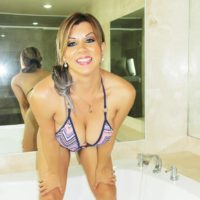 Trans model Naomi Chi slides bikini bottoms aside to expose her cock on side of a tub