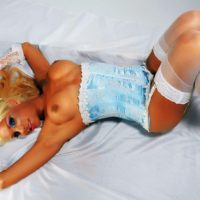 Blonde tranny Angeles Cid shows off her firm tits in lingerie and stockings on a bed