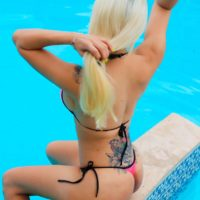 Blonde trans model Angeles Cid blows a kiss while wearing a bikini by the pool
