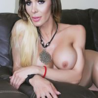 Busty tranny Nelly Ochoa flaunts her ass on a leather couch in sheer panthyhose