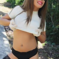 Trans babe Tania Quintilla bares her tits and ass outdoors with sunglasses on