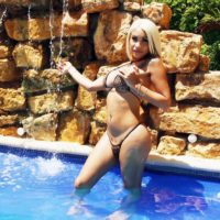 Beautiful blonde tranny Angeles Cid frees her big tits and cock from a bikini by a pool