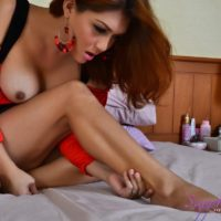 Redhead ladyboy Sapphire Young cums on the soles of her feet while jerking off
