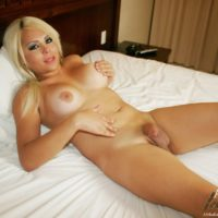 Pretty blonde trans girl Afrika Kampos plays with her big dick while naked atop a bed