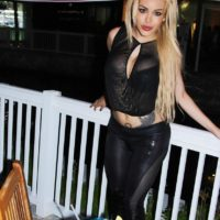 Beautiful blonde shemale Karla Carrillo sips a mixed drink on a patio while clothed