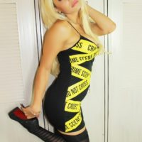 Blonde trans model Angeles Cid poses non nude in a little black dress and hosiery