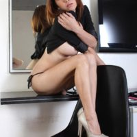 Redhead ladyboy Sapphire Young shows off her great legs while exposing firm boobs