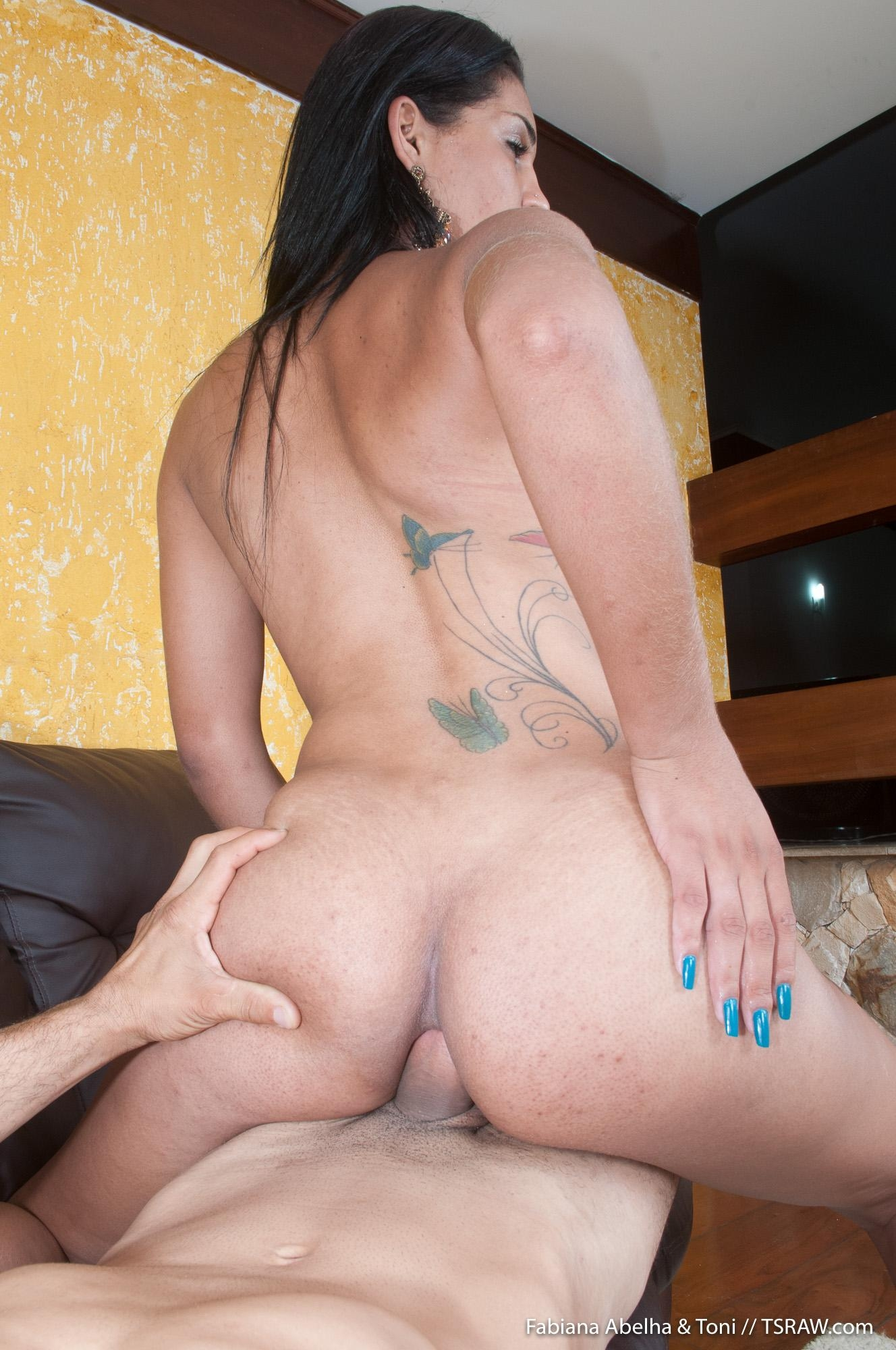 Latina shemale Fabiana Abelha tugs on her cock with a man's dick in her dirty asshole