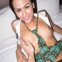 Cute ladyboy Lanta has sex with a man while in her schoolgirl uniform on a bed