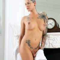 Barefoot trans model Danni Daniels displays her tattooed body while totally naked