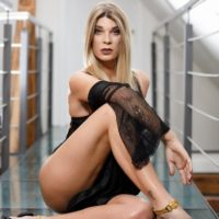 Blonde T-girl Angelina Torres sets her small breasts free off sensual lingerie by herself