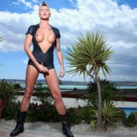 Leggy blonde transsexual Danni Daniels jerks her hard cock while outdoors in boots