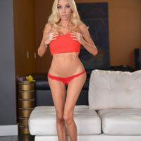 Long legged blonde transsexual Kimber James releases her large tits from a tube top