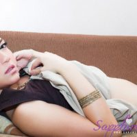 Redhead Asian ladyboy Sapphire Young jerks off during upskirt action upon a sofa