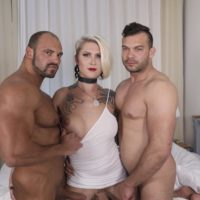Tattooed blonde tranny Danni Daniels has her hard cock jerked on by two men at once