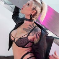 Tattooed blonde trans model Danni Daniels shows off her long legs in a leather jacket