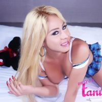 Ash-blonde Latina Tgirl Tania Quintilla plays with her rock hard penis on a bed in knee socks