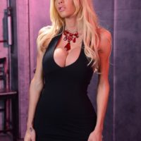 Busty post-op transsexual Kimber James showcases her pussy on a chair in red heels