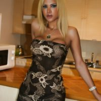 Pretty platinum-blonde Shemale Milla Viasotti releases her gigantic breasts from a cock-squeezing sundress in the kitchen