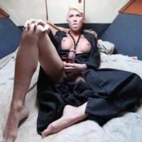 Short haired blonde shemale Danni Daniels spreads her long legs for her male lover