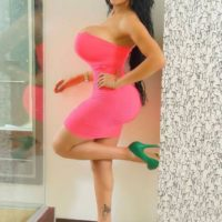 Trans model Azeneth Sabrok fills out a clingy pinkish sundress during a safe for work shoot