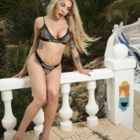 Leggy blonde shemale Eva Paradis exposes her tits and cock while on a balcony