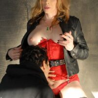 Redheaded transsexual Jasmine Jewels smokes a cigarette while a man sucks on her penis