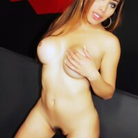 Trans solo model Nina Stronghold letting her perfect knockers loose from within a black dress