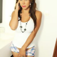 Solo trans model Naomi Chi lets her ample figure from a tank top and shorts
