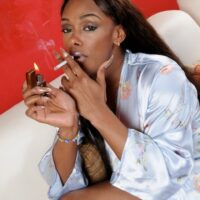 Black trans model Natalia Coxxx smokes a cigarette after posing totally naked